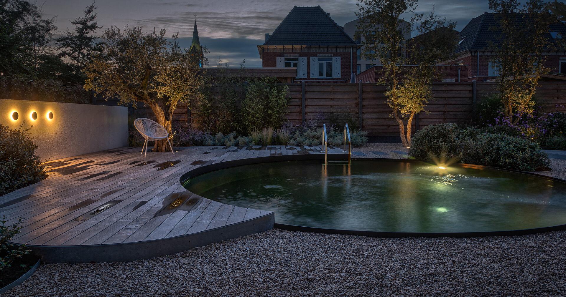 Biotop rond natuurzwembad met houten planken in het donker