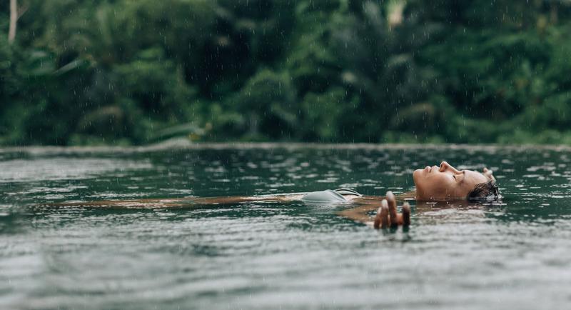 Vrouw in een natuurzwembad die geniet van natuurlijk water