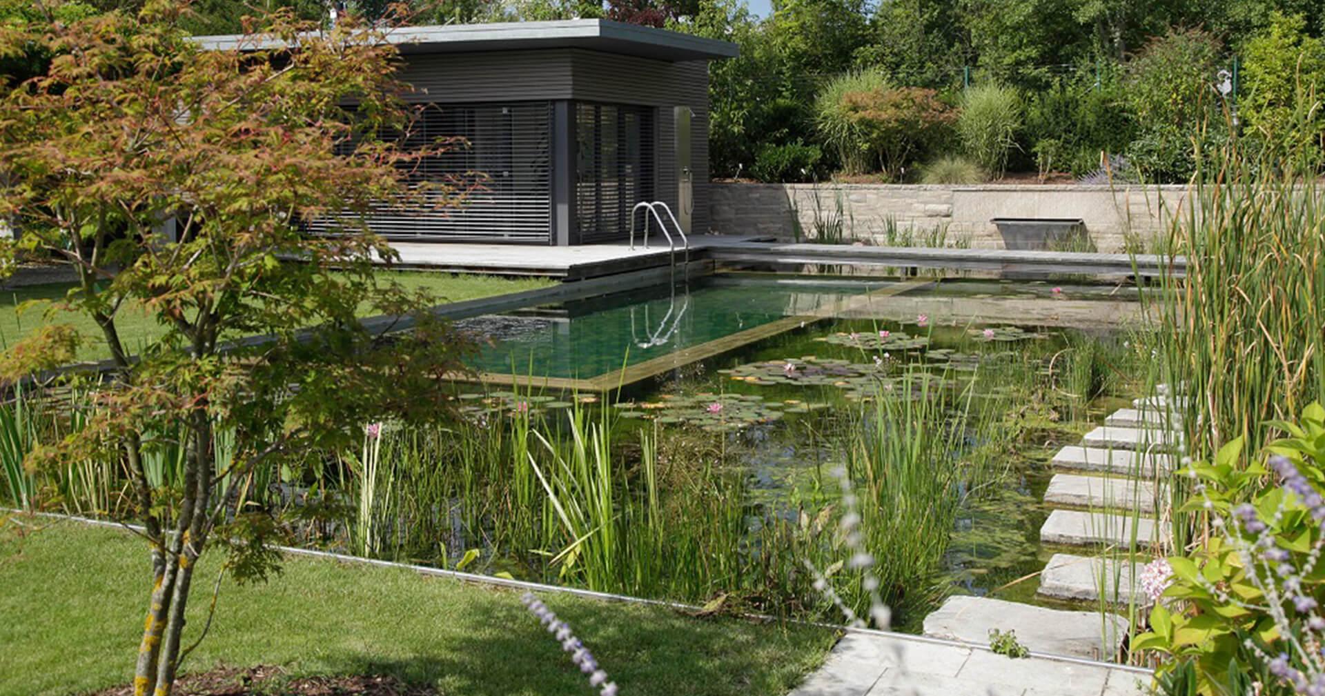 Zwemvijver in de tuin met loopstenen en een waterval
