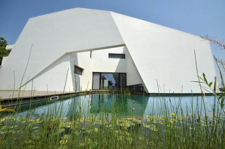 Zwemvijver bij een bedrijf met een groot wit gebouw op de achtergrond